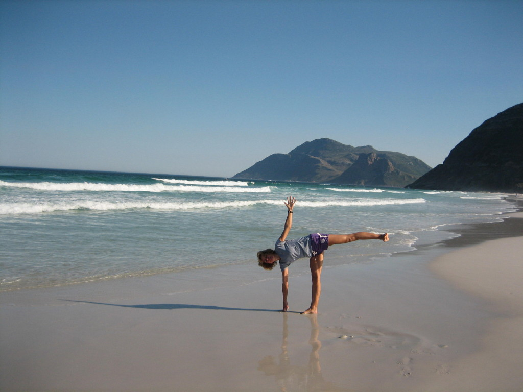 Charmaine in Halfmoon yoga pose on the beach